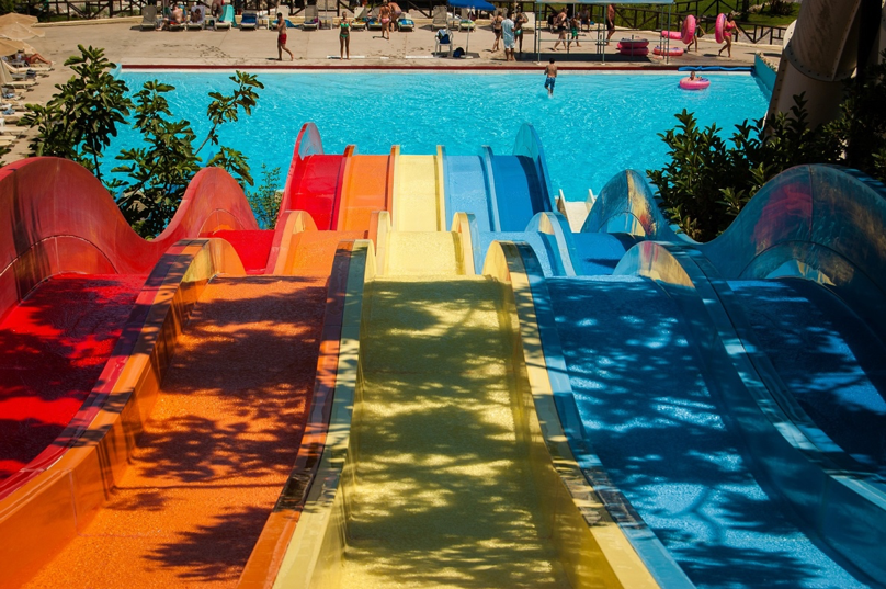 Five hilly waterslides in red, orange, yellow, and blue with a sparkling blue swimming pool at the bottom