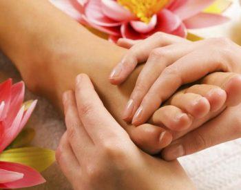 Foot massage - pair of hands massaging a foot