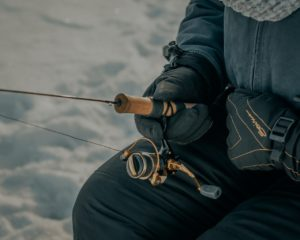A person sitting on ice, holding a fishing rode with gloves and a coat on.