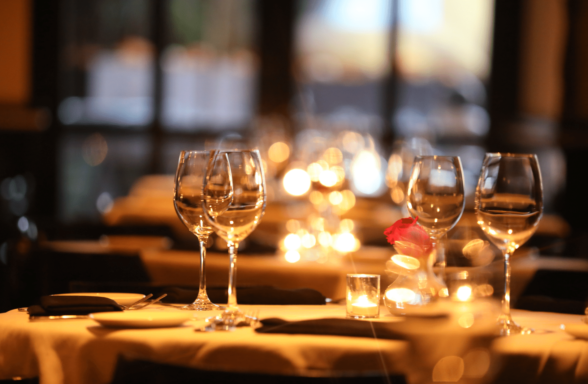 Fine dining restaurant table setting with wine goblets and dishes