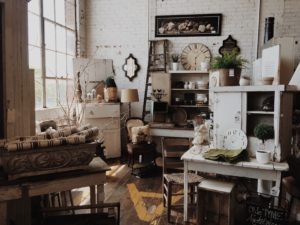 A naturally-lit room filled with neutral-toned antiques and home decor.