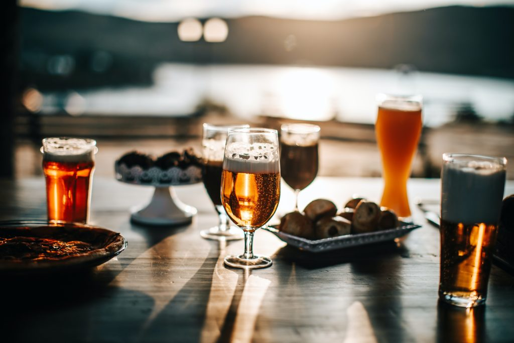Several glasses of beer and trays of food on a table overlooking a body of water.