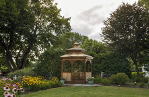 Wooden gazebo surrounded by green trees and lawn with purple and yellow flowers