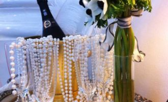 Champagne bottle in ice bucket and vase of flowers