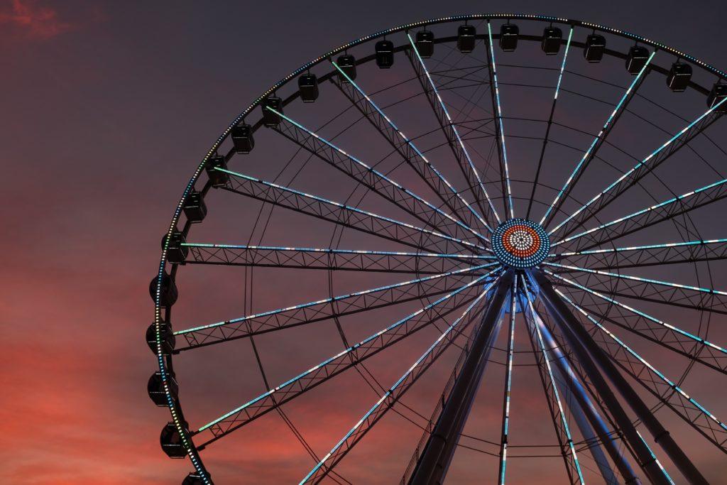 Large ferris wheel lit up at dusk