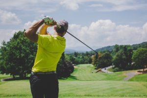 A man swinging a golf club under blue skies.