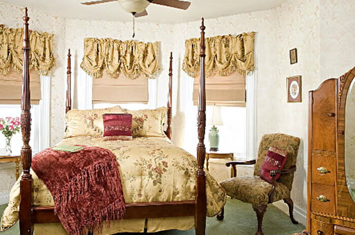 Large 4 poster bed with soft bedding, in room ith three windows and green carpet