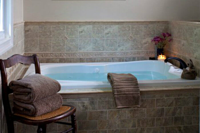 Large white step-in tub surrounded by brown tile with chair with towels on it