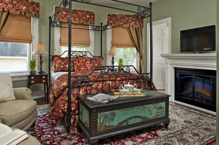 Large iron bed with red and yellow bedding