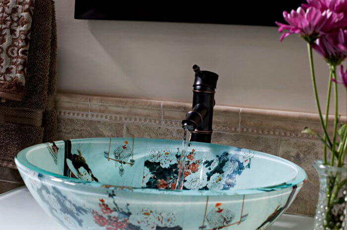Glass sink bowl with Asian figures on tile countertop