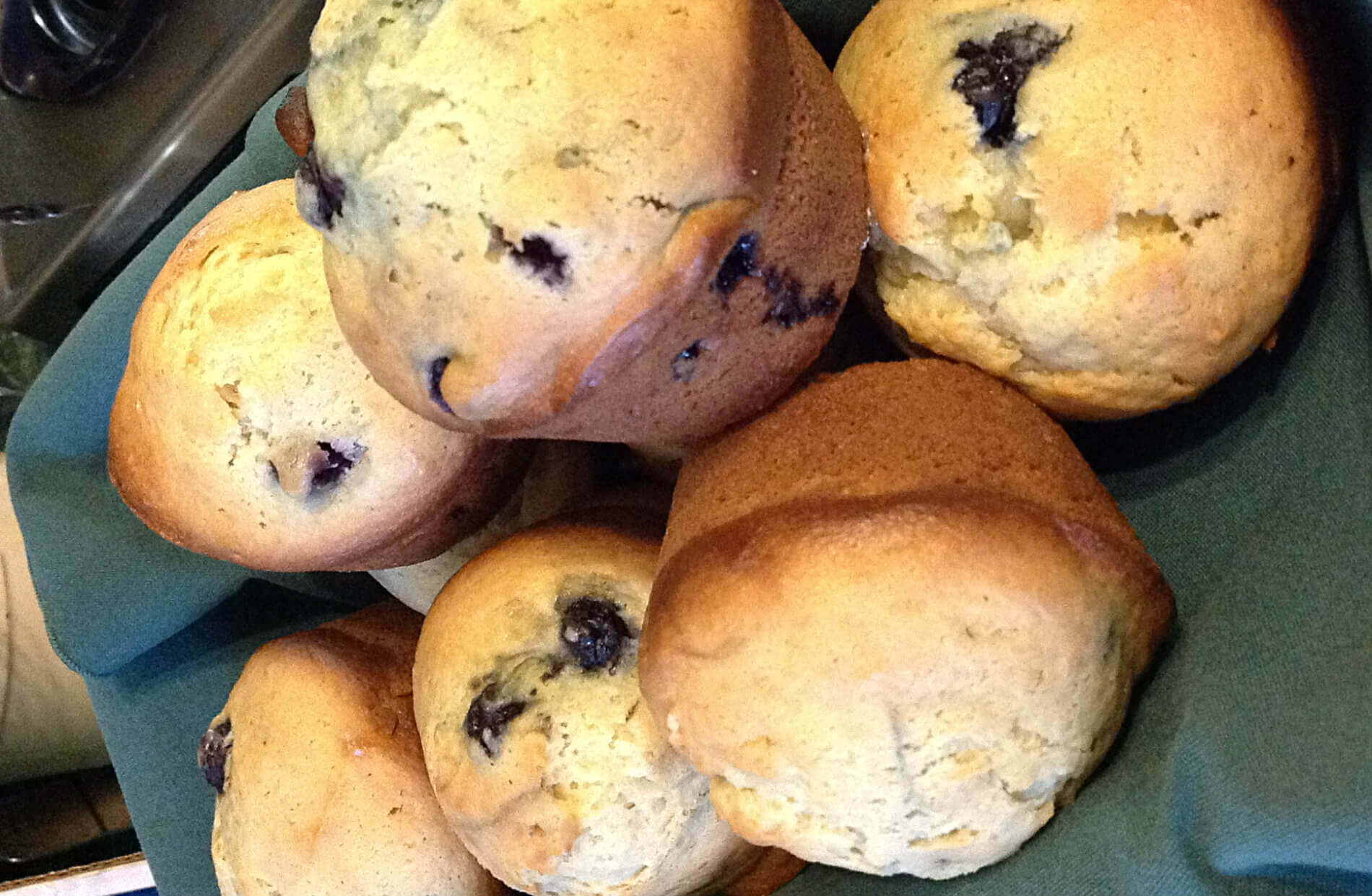 Blueberry muffins in basket with green cloth liner