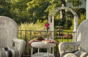 White wicher lawn furniture on porch with view of white arch in garden