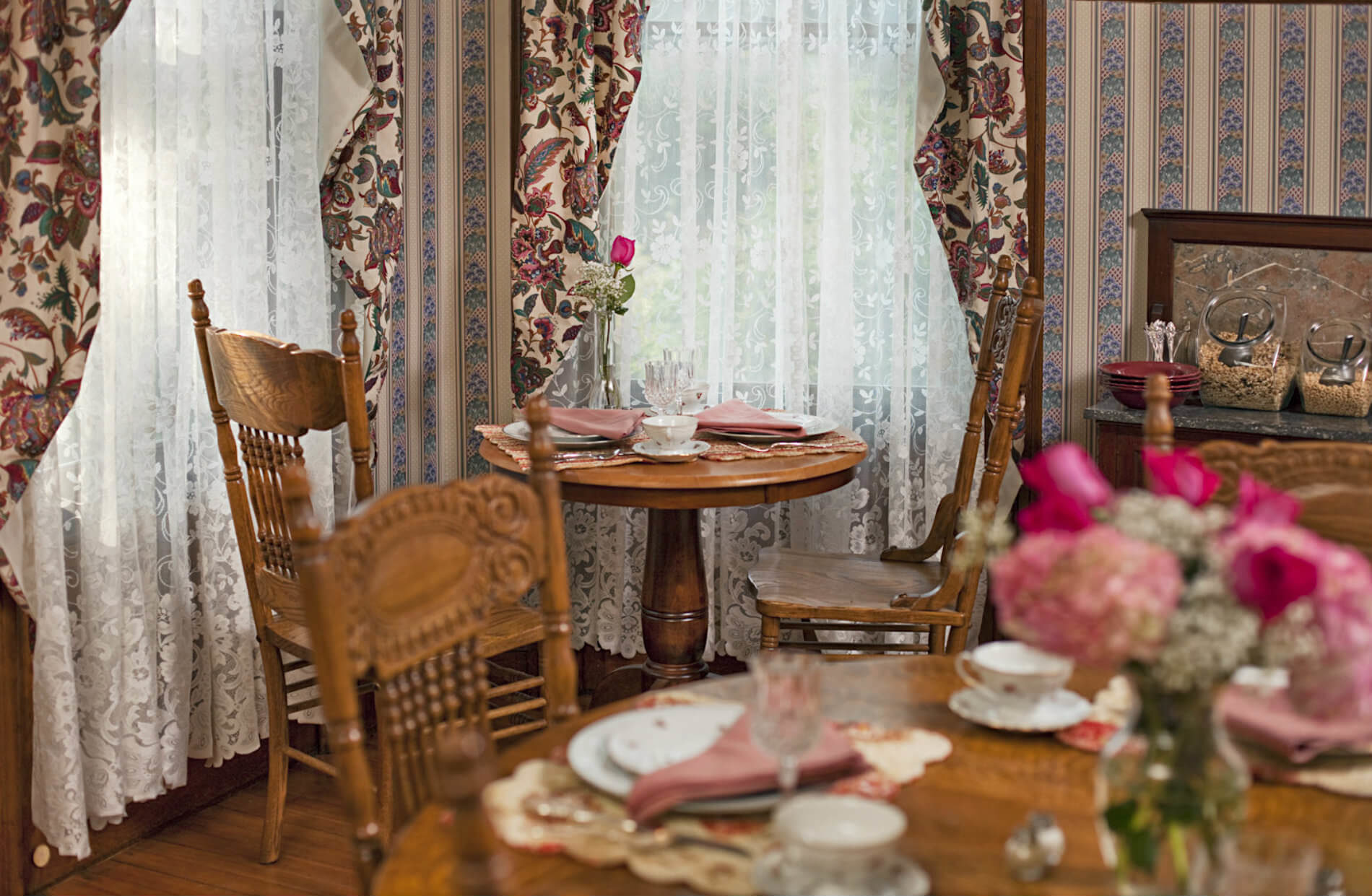 Wooden tables with plates and tea cups with a floral pattern