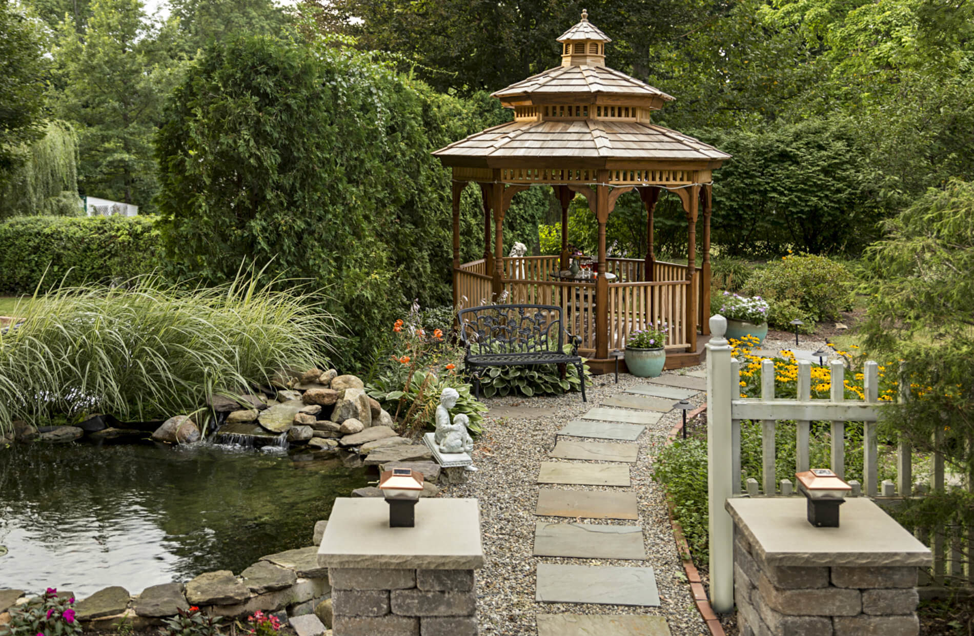 Stone path leading to wooden gazebo with green hedge in background