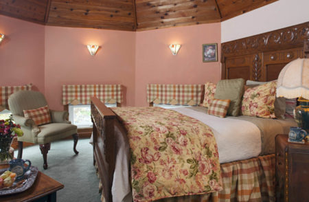 Peach walled room with wooden bed with soft flowered bedding