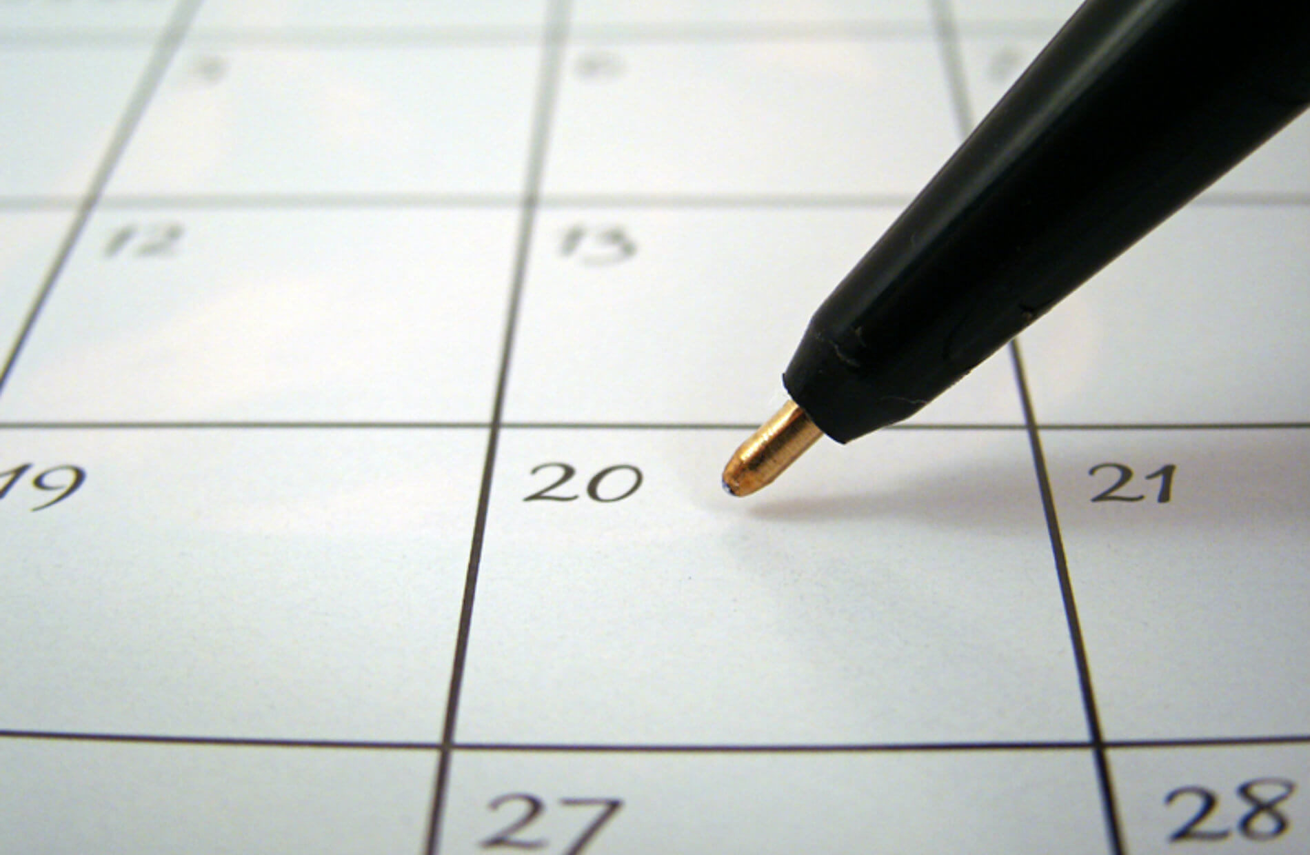 Black pen poised over the 20th on a calendar
