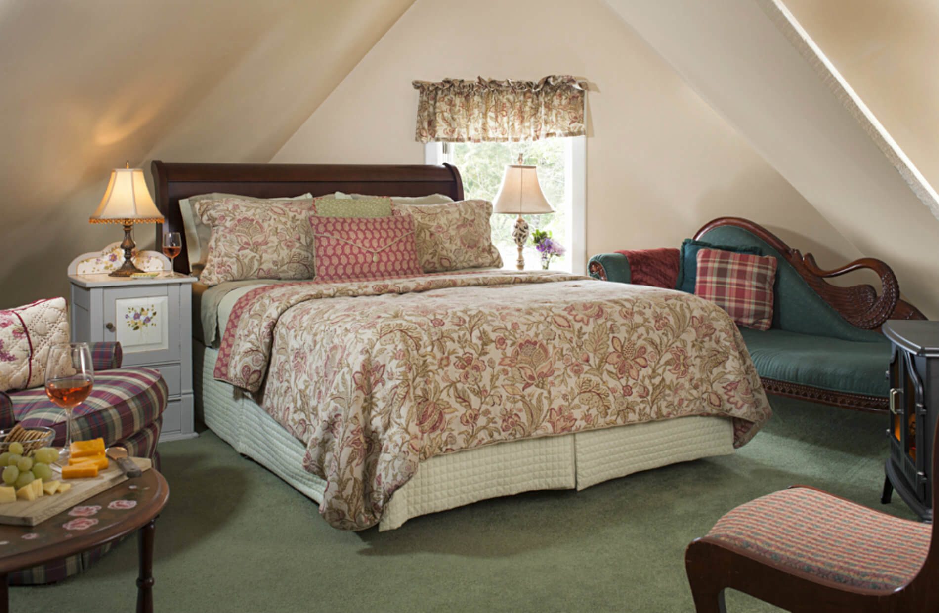 Wooden bed in gabled room with green carpet