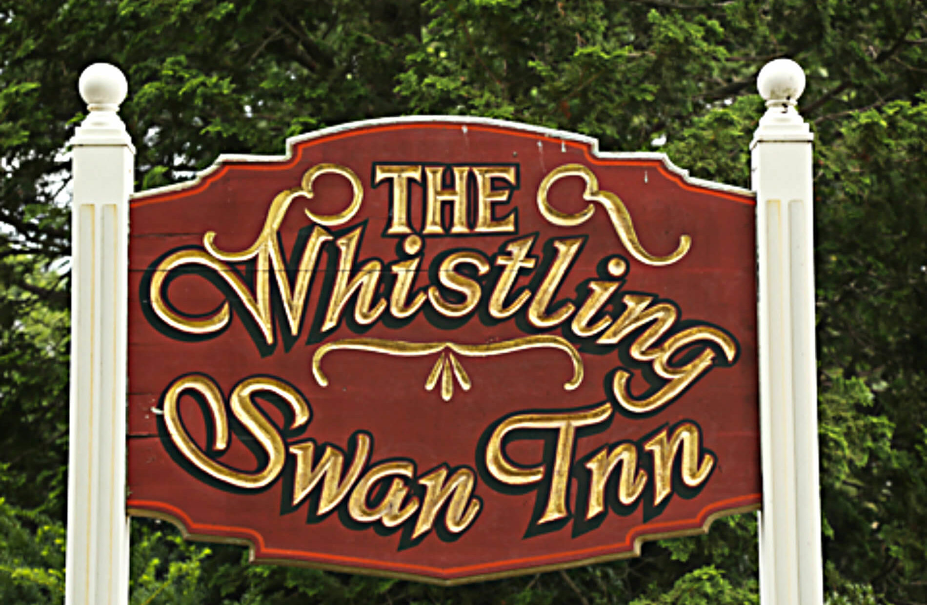 Large Exterior red sign with gold words: The Whistling Swan Inn