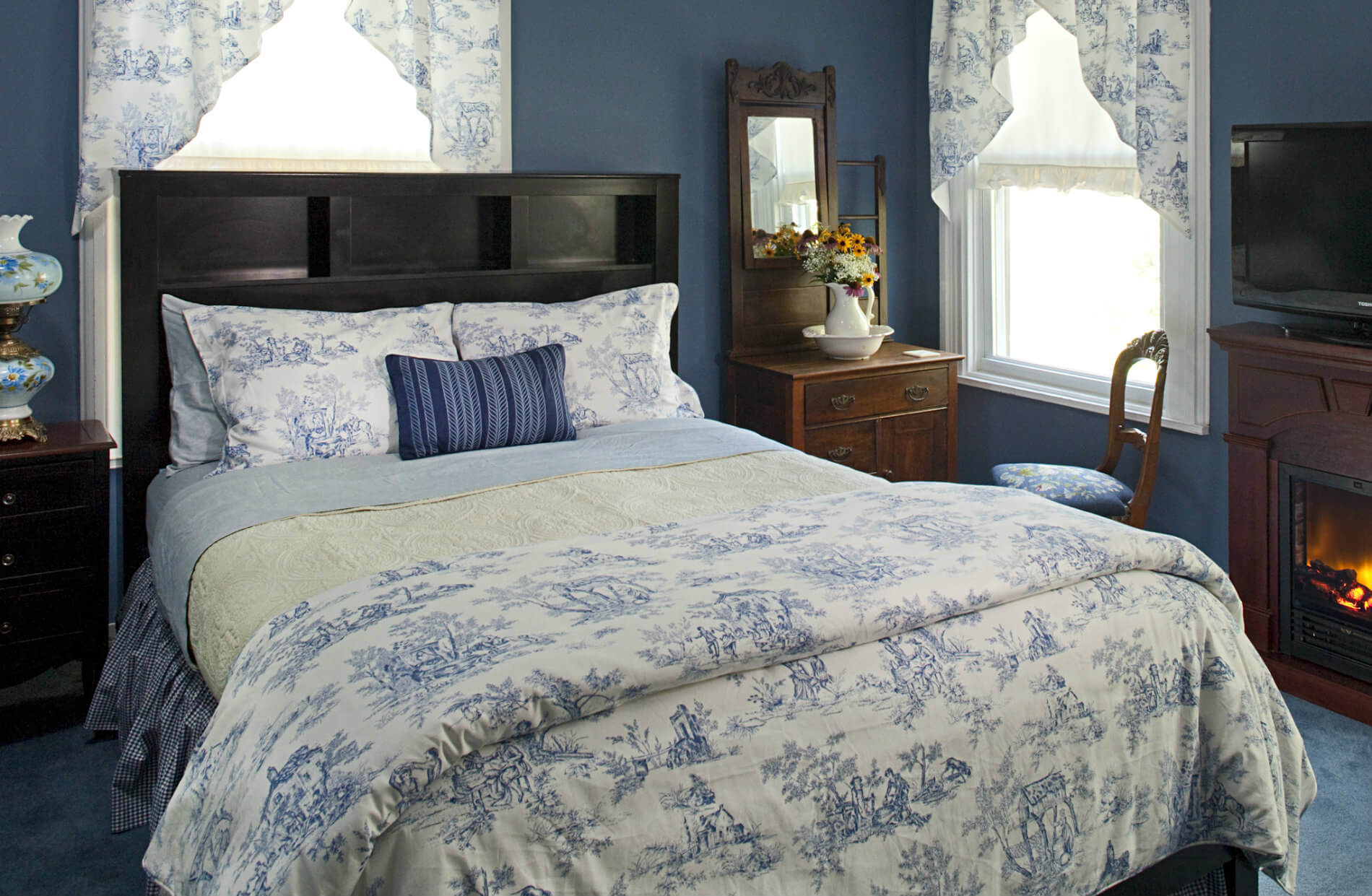 lue room with white curtains and large bed with white and blue bedding