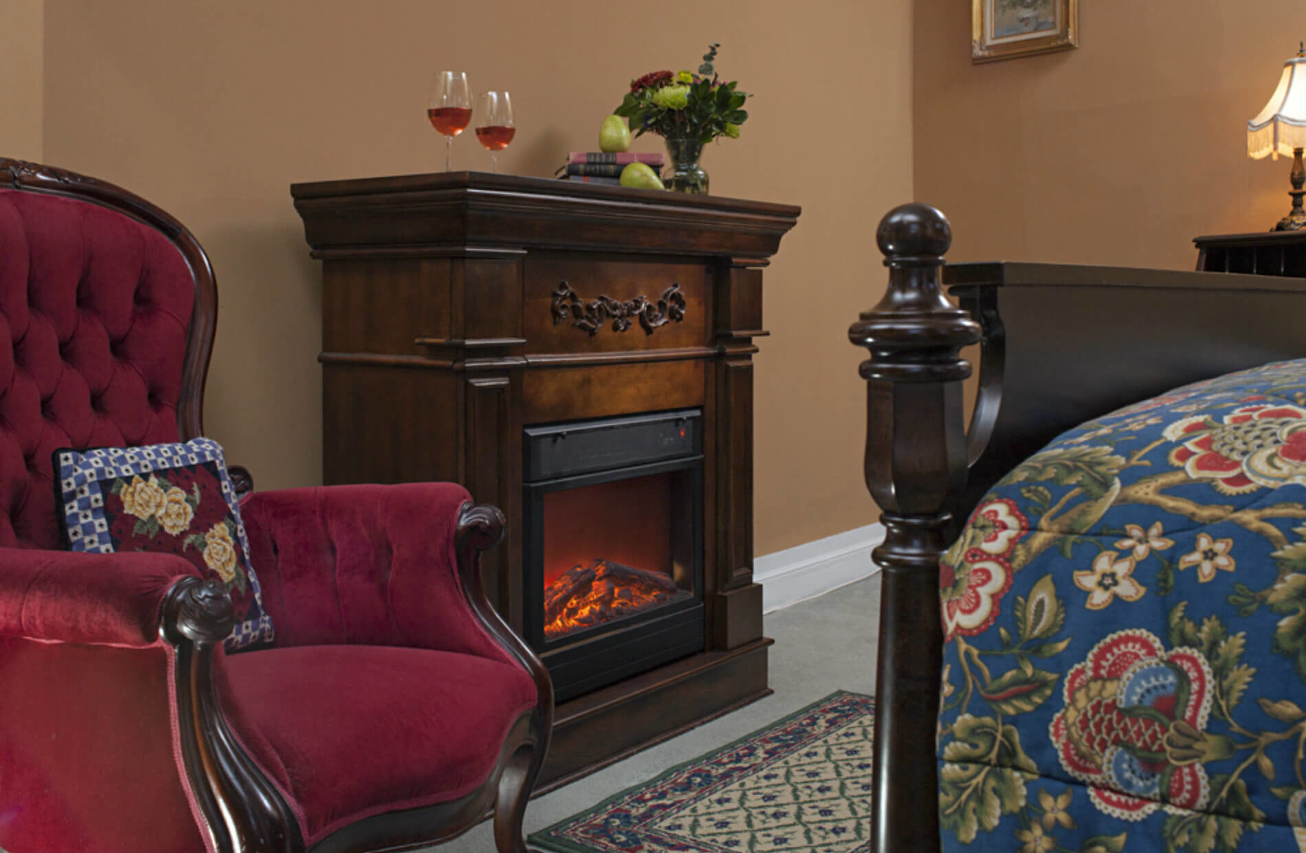 Wooden fireplace next to red wingback chair in tan walled bedroom