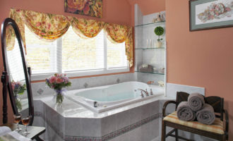 Deep step-in tub in room with peach walls with large window over it