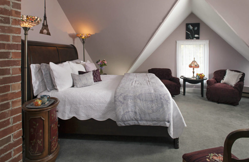 White room with gabled roof and wooden bed with white bedding