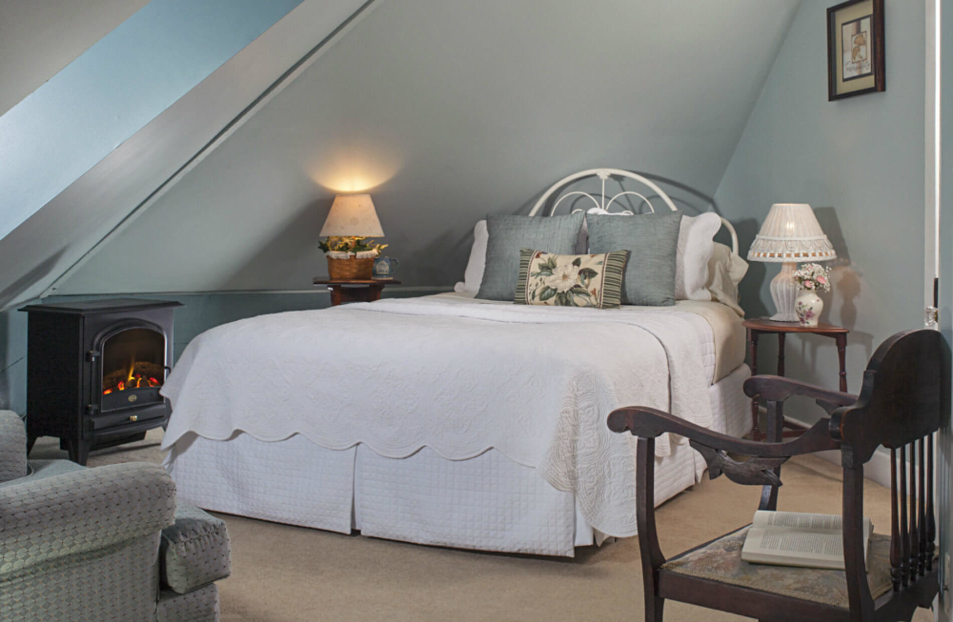 Large bed with white coverlet in gabled ceiling room with lamp