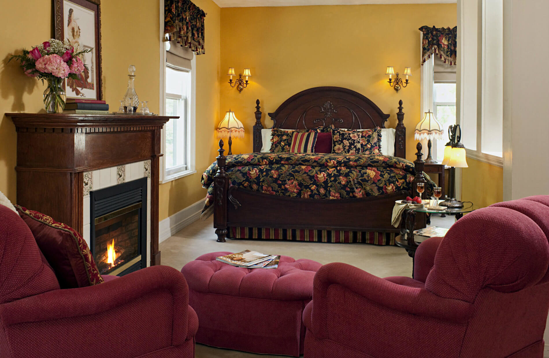 Gold walled room with large wooden bed with drk bedding and two red wingback chairs