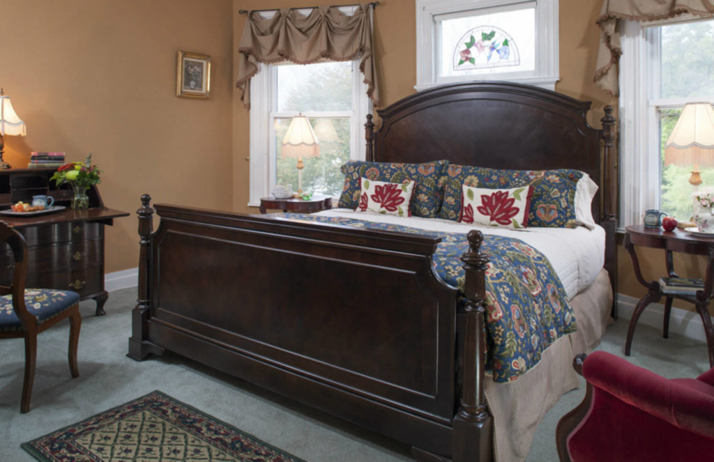 Serene Waterloo Village guest room with caramel walls, dark wood bed, secretary desk, night stands and natural light