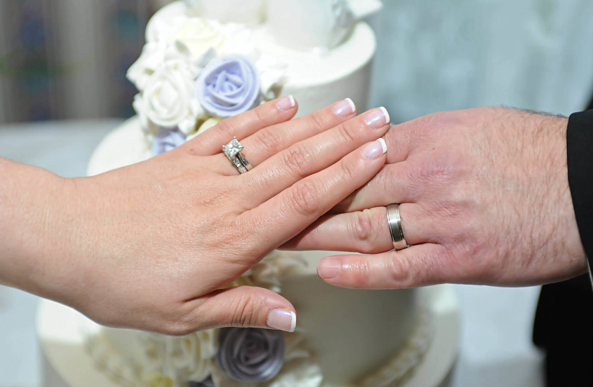 Hands of bride and groom with silver wedding rings in front of white two tier cake with lavender roses