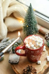 A mug of hot chocolate filled with marshmallows next to a window with cozy surroundings.