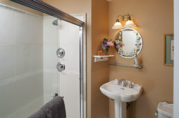 White tile shower in peach walled bathroom with white vanity