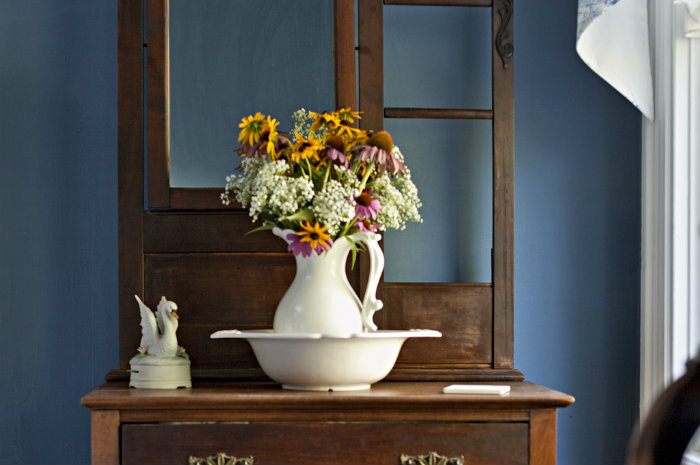 Antique wooden bureau with white ewer and basin full of flowers