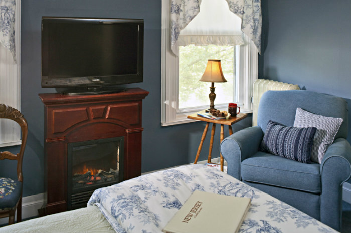 View from bed of room with blue walls, flat screen tv over wooden fireplace and puffy blue chair