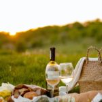 A sunset picnic setup with wine and two glasses over a blanket in the grass.