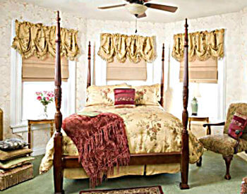 Large bed with yellow bedding surrounded by 3 windows with matching valances