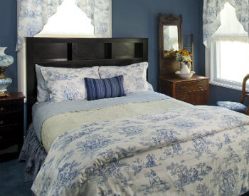 queen bed with French blue toile bedding and curtains