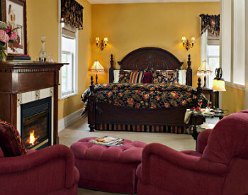 king bed with black floral bedding, gold walls and 2 chairs