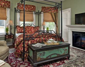Large 4 post bed in red and yellow bedding on oriental rug in room with two windows