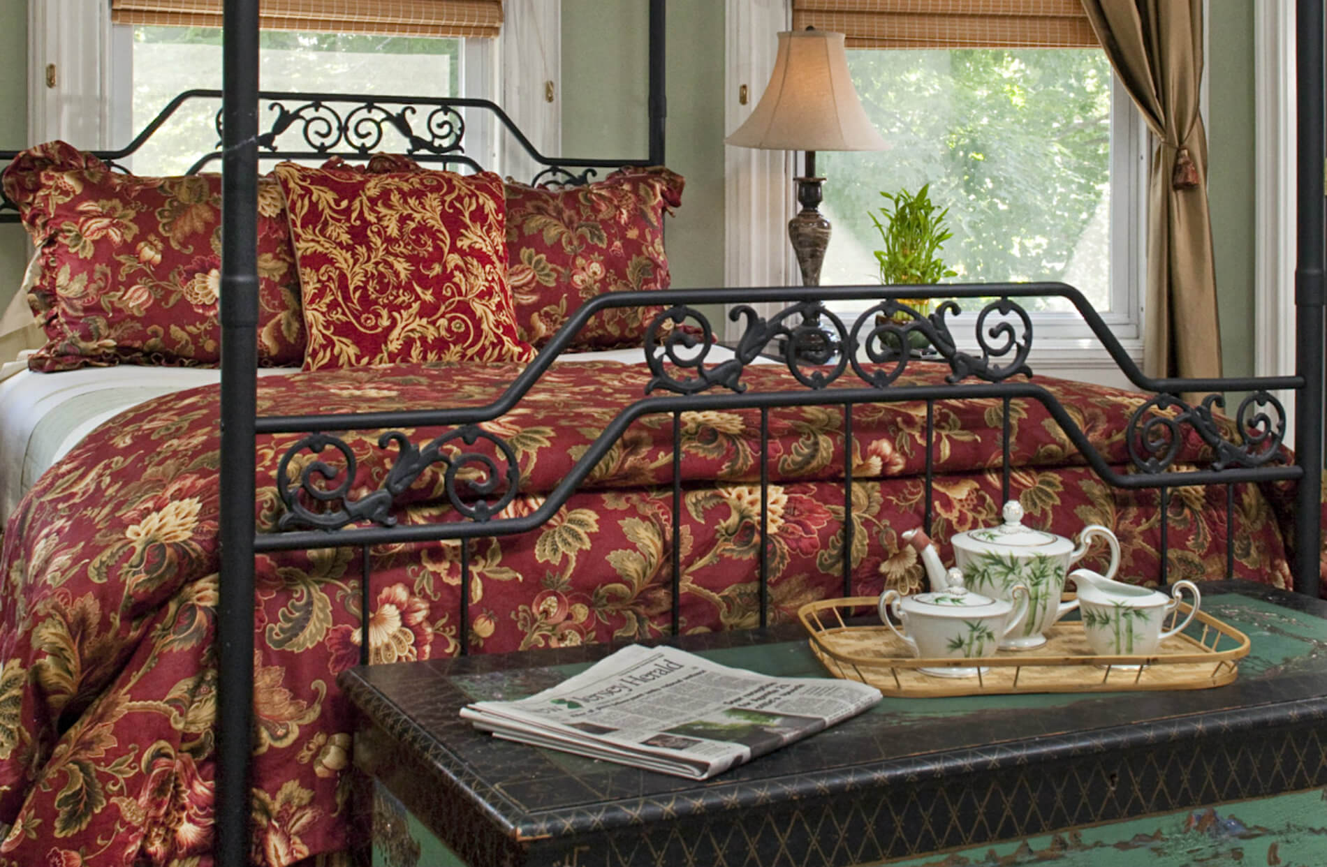 Iron bed with red and gold bedding and seat at foot of bed