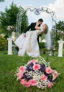 Bride and groom in an embrace. Foreground is a pink rose and baby's breath bouquet. A green arch and two plinths are in the background