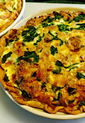 Egg quiche in white pie plate with spinch