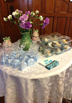 Round table with white damask cloth and flowers and party favors