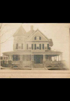 Old sepia photo of large house with large front porch and gabled roof