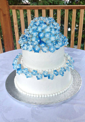 White two-story cake with blue violets on silver platter
