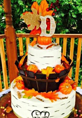 Large Fall-themed wedding cake with orange pumpkins and choclate surround