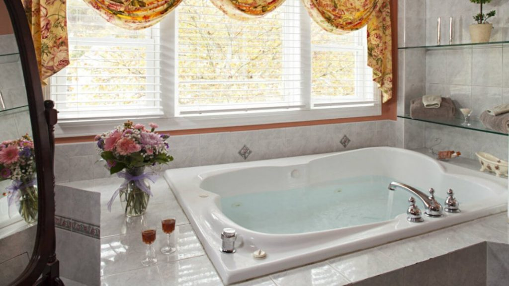A whirlpool tub with wine and a bouquet of flowers nearby.