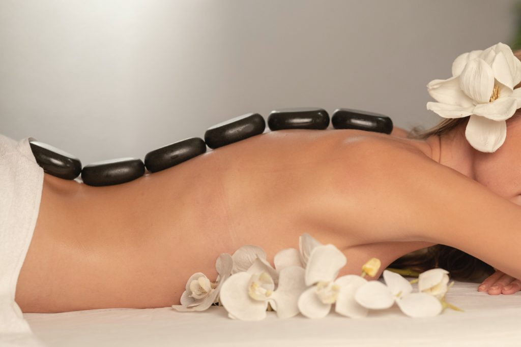 Woman laying on massage table with black stones arranged in a line down her back.