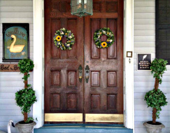 Large wooden doors with green topiaries on either side and gold kickplates