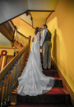 bride and groom on wooden Victorian staircase; gold walls